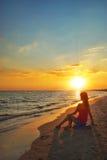 Muchacha que se sienta en la playa Imagenes de archivo