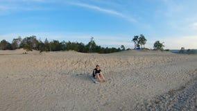Muchacha que se sienta en la playa arenosa y que dibuja un paisaje Tiro del card?n metrajes