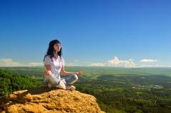 Muchacha que se sienta en la posición de loto respecto a la montaña Fotografía de archivo