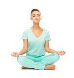 Muchacha que se sienta en la posición y meditar de loto Imágenes de archivo libres de regalías