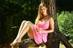 Muchacha que se sienta en la rama del pino, cerca del lago del bosque. Fotos de archivo