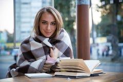 Muchacha que se sienta en la tabla con el libro y el café Fotografía de archivo