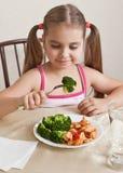 Muchacha que se sienta en la tabla y que busca la comida Foto de archivo