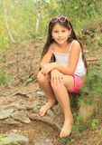Muchacha que se sienta en la tierra Imagen de archivo