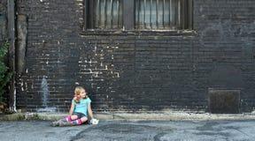 Muchacha que se sienta en la tierra al lado de la pared de ladrillo Imagenes de archivo
