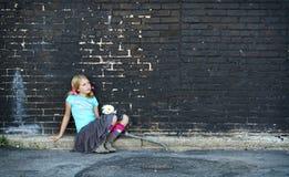 Muchacha que se sienta en la tierra al lado de la pared de ladrillo Fotos de archivo