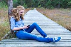 Muchacha que se sienta en la trayectoria de madera en la naturaleza que llama por teléfono al móvil Fotos de archivo