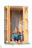Muchacha que se sienta en la ventana Imágenes de archivo libres de regalías