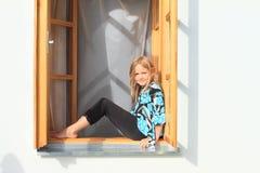 Muchacha que se sienta en la ventana Fotos de archivo