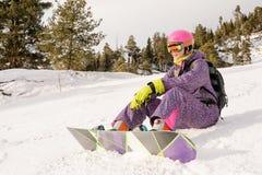 Muchacha que se sienta en las cuestas del esquí Fotografía de archivo libre de regalías
