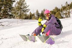 Muchacha que se sienta en las cuestas del esquí Foto de archivo libre de regalías