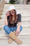 Muchacha que se sienta en las escaleras Imagenes de archivo