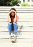 Muchacha que se sienta en las escaleras Foto de archivo libre de regalías