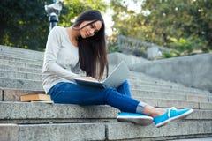 Muchacha que se sienta en las escaleras de la ciudad con el ordenador portátil al aire libre Imágenes de archivo libres de regalías