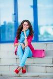 Muchacha que se sienta en las escaleras en ropa colorida Imagen de archivo libre de regalías
