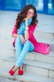 Muchacha que se sienta en las escaleras en ropa colorida Imágenes de archivo libres de regalías