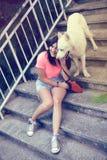 Muchacha que se sienta en las escaleras y que juega con su perro fornido Foto de archivo