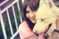 Muchacha que se sienta en las escaleras y que juega con su perro fornido Imagen de archivo libre de regalías