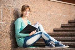Muchacha que se sienta en las escaleras y que lee la nota Imagen de archivo libre de regalías