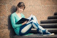 Muchacha que se sienta en las escaleras y que lee la nota Fotos de archivo libres de regalías