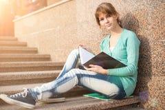 Muchacha que se sienta en las escaleras y que lee la nota Foto de archivo