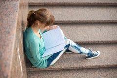 Muchacha que se sienta en las escaleras y que lee la nota Imagenes de archivo