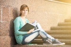 Muchacha que se sienta en las escaleras y que lee la nota Fotografía de archivo