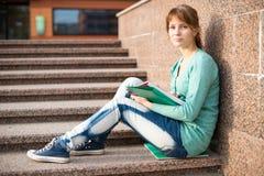 Muchacha que se sienta en las escaleras y que lee la nota Foto de archivo libre de regalías