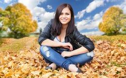Muchacha que se sienta en las hojas de otoño Foto de archivo libre de regalías