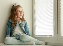 Muchacha que se sienta en las persianas cerradas Foto de archivo libre de regalías