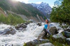 Muchacha que se sienta en las rocas en el río de la montaña Foto de archivo