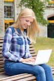 Muchacha que se sienta en parque con el ordenador portátil Imagen de archivo