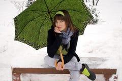 Muchacha que se sienta en parque del invierno Fotos de archivo