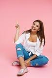 Muchacha que se sienta en piso en el equipo de moda que sonríe en la cámara Imagen de archivo