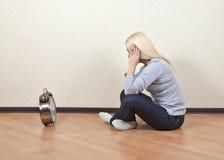 Muchacha que se sienta en piso y miradas en la suya reloj Fotos de archivo libres de regalías