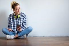Muchacha que se sienta en piso y que usa smartphone Imágenes de archivo libres de regalías