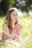 Muchacha que se sienta en planta del diente de león del campo del verano que sopla Fotos de archivo libres de regalías