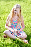 Muchacha que se sienta en prado con un jarro de leche Fotografía de archivo libre de regalías