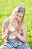 Muchacha que se sienta en prado con un jarro de leche Imagen de archivo