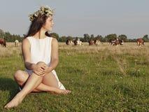 Muchacha que se sienta en prados de la hierba Imagenes de archivo