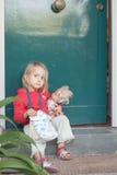Muchacha que se sienta en puerta principal imagenes de archivo