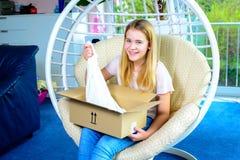 Muchacha que se sienta en silla y que abre un paquete Foto de archivo
