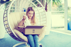 Muchacha que se sienta en silla y que abre un paquete Fotografía de archivo