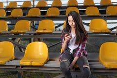 Muchacha que se sienta en soportes y miradas en un teléfono móvil Foto de archivo