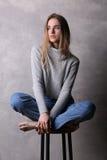 Muchacha que se sienta en suéter con las piernas cruzadas Fondo gris Imagenes de archivo