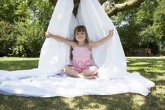 Muchacha que se sienta en tienda de la hoja en patio trasero Foto de archivo libre de regalías