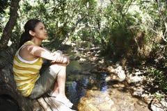 Muchacha que se sienta en tronco de árbol por la corriente Foto de archivo libre de regalías