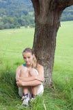 Muchacha que se sienta en un árbol Imagenes de archivo