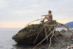 Muchacha que se sienta en un acantilado y que mira el agua del Mar Negro Imágenes de archivo libres de regalías