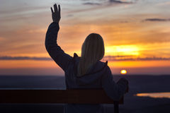 Muchacha que se sienta en un banch en la puesta del sol Imagenes de archivo